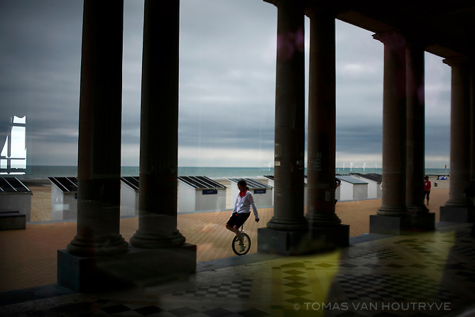 A girl on a unicycle is reflected in the window of the Thermae Palace Hotel, the former coastal palace built for King Leopold II in Ostend, Belgium on 28 August, 2008.