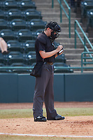 Home plate umpire Sean Cassidy makes notes during the South Atlantic League game between the Lakewood BlueClaws and the Hickory Crawdads at L.P. Frans Stadium on April 28, 2019 in Hickory, North Carolina. The Crawdads defeated the BlueClaws 10-3. (Brian Westerholt/Four Seam Images)