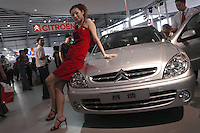 A Chinese model poses besides a Citroen Xsara at the Auto China 2004 exhibition in Beijing, China..