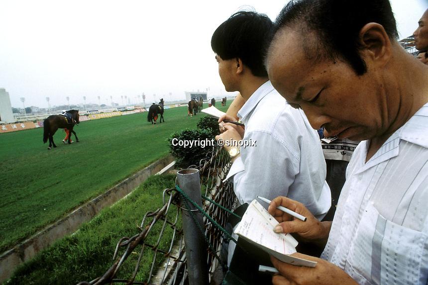 Men watch horse racing at Guangzhou race course.