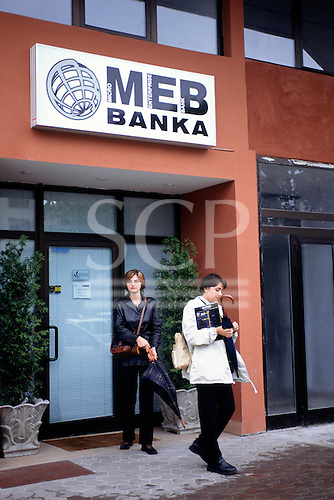 Sarajevo, Bosnia and Herzegovina. The entrance of the MEB Banka (Micro Enterprise Bank); people with umbrellas.