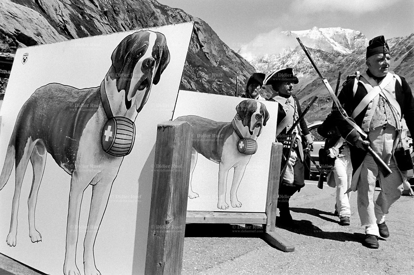 """Switzerland. Canton Valais. On the Great St. Bernard Pass. A group of men from the """" Voltigeurs du 3eme régiment suisse"""", all dressed with historic traditional soldiers outfits and muskets during a historical reenactment based on the crossing of the Great St. Bernard Pass on May 13, 1800 by Napoleon Bonaparte and his army on their way to attack the Austrian army in Italy. Two large drawings with St Bernard dogs with barrels. The St. Bernard or St Bernard is a breed of very large working dog from the western Alps. They were originally bred at the Great and Little St Bernard Pass for rescue. The breed has become famous through tales of alpine rescues, as well as for its enormous size. A musket is a muzzle-loaded, smoothbore long gun, fired from the shoulder. Muskets were designed for use by infantry. A soldier armed with a musket had the designation musketman or musketeer. Great St. Bernard Pass (French: Col du Grand St-Bernard, Italian: Colle del Gran San Bernardo, German: Grosser Sankt Bernhard; 2,469 m (8,100 ft)) is the third highest road pass in Switzerland. Great St. Bernard is one of the most ancient pass through the Western Alps. 12.08.2017 © 2017 Didier Ruef"""