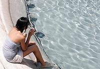 Una turista si rinfresca ad una fontana per ripararsi dal caldo, a Roma, 17 luglio 2010..A tourist cools off at a fountain in a hotsummer day in Rome, 17 july 2010..UPDATE IMAGES PRESS/Riccardo De Luca