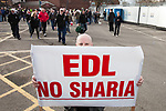 "© Joel Goodman - 07973 332324 . 25/02/2012 . Hyde , UK . A man holds a banner reading "" EDL No Sharia "". The EDL demonstrate following an assault on Daniel Stringer-Prince, whose family say they do not want the demonstration to take place in the town in their son's name. The EDL say Daniel was assaulted by a gang of Asian men . At the same time , the BNP hold a rally in the town . Photo credit : Joel Goodman"