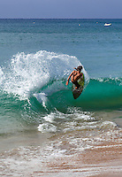 A skimboarder doing a 360-degree turn at Ka'anapali Beach, Maui.