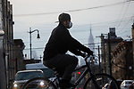 A man wearing a face mask rides his bike with the Empire State building in the background during the coronavirus pandemic (COVID-19) in the Brooklyn borough of New York City on April 5, 2020.  Photograph by Michael Nagle
