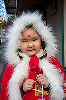 Cute asian girl wearing traditional clothing, Chinese New Year Celebration, Chinatown, Seattle, WA, USA.