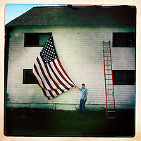 A campaign volunteer secures an American flag on a farm in Stratham, New Hampshire,  where former Massachusetts Governor Mitt Romney's announced he is running for the 2012 U.S. Republican presidential nomination.