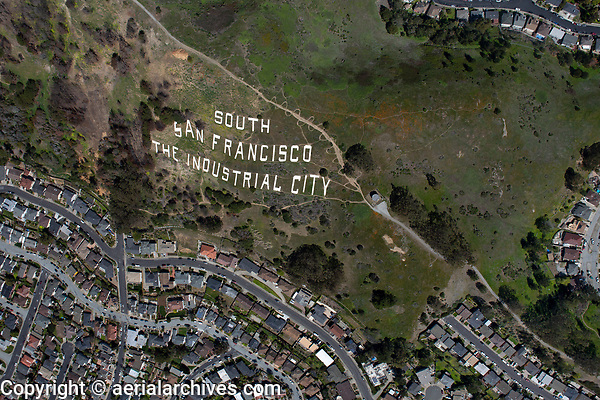 aerial photograph San Bruno Mountain, South San Francisco, San Mateo County, California in spring.  One of the trailheads to San Bruno mountain is located at at the right, trail switchbacks run along the northern side of the South San Francisco The Industrial City sign.