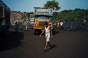 A labourers walks past the trucks waiting to load up the coal in Goladi coal depot in Jharia, outside of Dhanbad in Jharkhand, India.  Photo: Sanjit Das/Panos