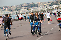 Cyclists on 'velos bleus' (Nice's share bike scheme) ride on the Promenade des Anglais, Nice, France, 28 April 2012