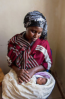 Africa, DRC, Democratic Republic of the Congo, Goma, Lake Kivu, Hotel Cap Kivu. Global Fund for Women. PAIF project. Dusabe Tumaini (32 years), Rehema (baby, one week). I'm from Masis in the Congo, where 90% of the women are raped and many people are killed everyday. There's no presence of government there, only bandits, locals carrying guns. I was married with 7 children. One day I went into the forest to collect firewood and I was attacked and raped by four men in military uniforms. They left me to die but some local villagers found me and brought me to a hospital. I didn't want anyone to know I had been raped but it was soon discovered that I was pregnant. When my husband found out I was raped he ran away and left me with the 7 children. He was afraid of AIDS. And when he found out I was pregnant he didn't want to raise someone else's baby. Eventually his family and our pastor talked him into returning. Rehema was born a week ago. Now we say we have 7 children and this one. My husband said at least it's girl, she can be useful and work and bring in cows when she marries. <br /> PAIF has helped to move away from that terrible area and we now live in their temporary housing in Goma. Because we're displaced people the children don't go to school.  My life changed that day I went to collect firewood in the forest.