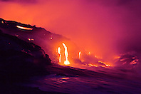 Hot molten lava entering into Pacific Ocean, creating new land and massive steam clouds, Lae`apuki lava delta crated from continuous eruption of Pu`u `O`o Crater, Hawaii Volcanoes National Park at night, Kilauea, Big Island, Hawaii, Pacific Ocean..