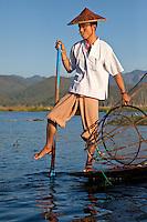Myanmar, Burma.  Fisherman Rowing with One Leg, Inle Lake, Shan State.