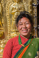 Nepal, Kathmandu, Swayambhunath.  Nepali Woman in front of Buddhist Shrine.  She wears a nose pin, and a bindi.  The red line between the part in her hair symbolizes that she is married.