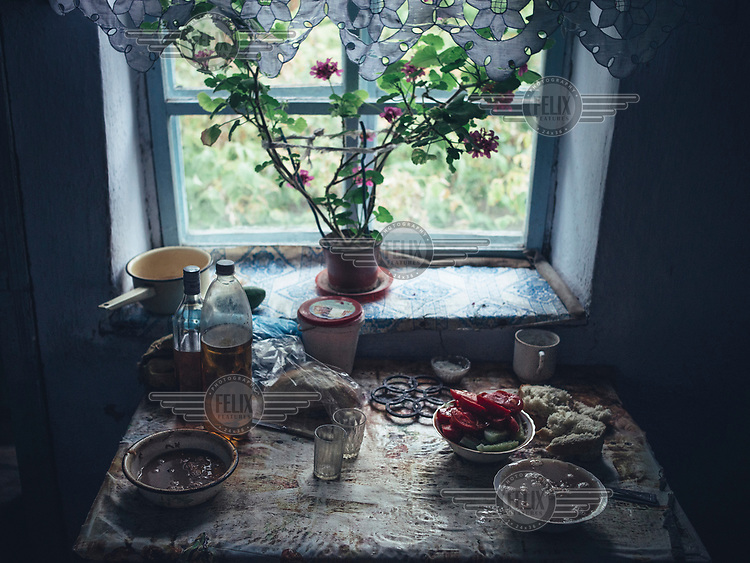 Bread, oil and tomatoes on a table beside a window in a rural home.