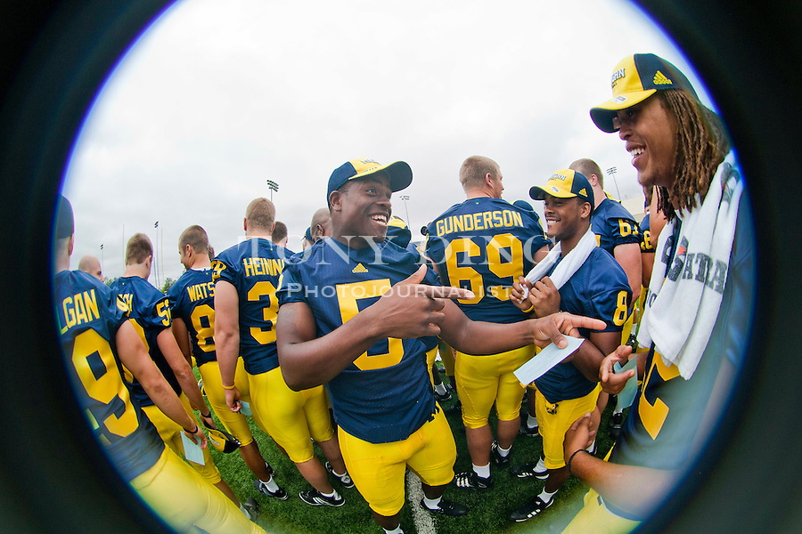 Michigan safety Vladimir Emilien (5) jokes around with slot receiver Terrence Robinson (8) and cornerback J.T. Floyd, right, at the annual NCAA college football media day, Sunday, Aug. 22, 2010, in Ann Arbor, Mich. (AP Photo/Tony Ding)
