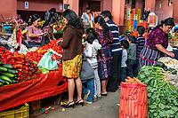 Chichicastenango, Guatemala.  Family  Buying Fresh Vegetables in the Indoor Market.
