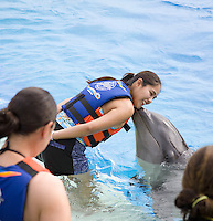 Tourist woman getting kissed by a dolphin at Hawaii Sea Life Park's Dolphin Swim program