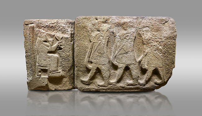 Alaca Hoyuk Sphinx Gate Hittite monumental relief sculpted orthostat stone panel. Andesite. Alaca, Corum, 1399 - 1301 B.C. Anatolian Civilizations Museum, Ankara, Turkey.<br /> <br /> Left Panel - Sitting in a chair without a backrest, the head and the face of the figure are completely destroyed. She has a long veil on her head, a long dress hanging down to her ankles, and the shoes with the curved ends. The stool under her feet indicates that she is an important person. She drinks something from the vessel in her right hand and she keeps the handled goblet in her hand a little higher.  <br /> <br /> Right Panel - Three figures with short skirts have their right arms positioned ahead. They each carry a sceptre in their left hand, which they lean against their shoulder. <br /> <br /> Against a brown gray background.
