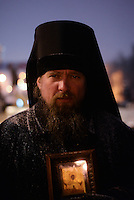 An orthodox priest  under the snow shows his support to  the  protest with an image of the Virgin Mary.  Kiev. Ukraine