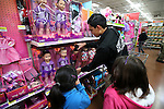Carson City Sheriff's Office Explorer Alejandro Cortez helps two of nearly 170 elementary students shop as part of the Holiday with a Hero program at Walmart in Carson City, Nev., on Tuesday, Dec. 17, 2013. The community event partners military, firefighters, law enforcement and medical personnel with local Students in Transition to provide them with Christmas presents.<br /> Photo by Cathleen Allison