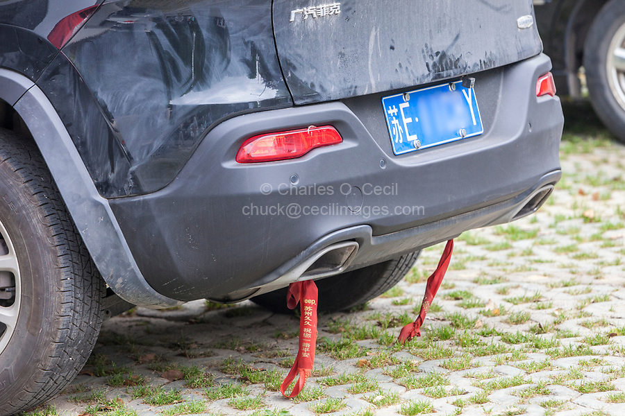 Suzhou, Jiangsu, China.  Chinese Custom: Tying Colored Fabric on Bumper of Car Gives Protection against Accidents.