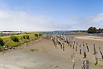 The Coquille River is banked by an abandoned dike and ruins of old piers as it enters the Pacific Ocean at the town of Bandon on the Oregon coast.