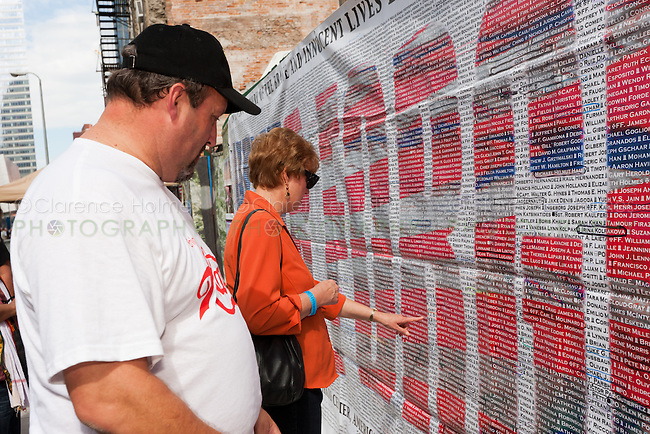 Visitors search for names on the list of those who perished in the 9/11 terrorist attack of the World Trade Center.  The list is posted on Greenwich Street across from the entrance to the National September 11 Memorial.