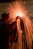 A welder works with a cuting torch.