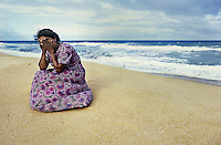 Mother who lost her three children to the sea when the tsunami hit   <br /> Batticola, Sri Lanka<br /> Of the 8,000 residents of Batticaloa, 5,000 died. That's 60 percent of its population. The once-thriving beach-front village was surrounded by a lagoon so there was nowhere to run when the giant wave hit, just into more water. Saris and clothing were left embedded in the barbed wire set up to protect against wild animals, where many of the bodies were trapped in its grip. A few remnants were scattered: cooking pots, photographs with cracked glass, clocks stopped when the wave hit at 9:22, Buddhist statues which mysteriously remained standing. But mostly there was just rubble. Everywhere had its own ghosts. <br /> <indnt>I viewed the beach, cluttered with personal effects. Human bones had started to wash up. A woman walked alongside me who appeared to be in shock. As I turned to ask if she was all right she began madly gesticulating toward the sea, indicating that it had taken her two children. She, as so many I encountered, now lived with the image of seeing her family swept away and struggled with the profound guilt of being unable to hold onto her children. Beside herself with anguish she attempted to throw herself into the ocean. I pulled her back and held her as she wept. Inconsolable, she buried her face in the sand. Death is certainly more integrated with life in this part of the world, but there was no quantifying the universality of a mother's pain.