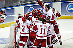 Junior Andy Brandt jumps over his teammates in celebration seconds after the UW Men?s Hockey team won the national championship.