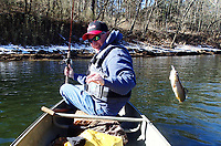 With snow still on the ground, Keith Brashers catches a rainbow trout Feb. 23 2021 during a float trip on the White River below Beaver Dam. Launching at the dam and floating to Houseman Access makes a fine 7-mile canoe trip.<br />(NWA Democrat-Gazette/Flip Putthoff)