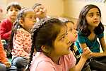 Education preschoool children ages 3-5 group of children seated on rug listening to story read by teacher (not visible) horizontal