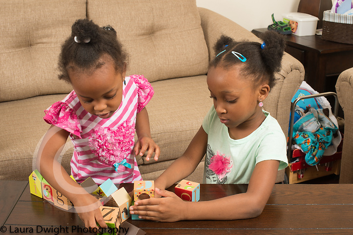 3 year old and 6 year old sisters at home playing with wooden block puzzle toy