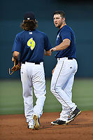 Left fielder Tim Tebow (15) of the Columbia Fireflies gets his hat and glove delivered to him by Gene Come (9) in a game against the West Virginia Power on Thursday, May 18, 2017, at Spirit Communications Park in Columbia, South Carolina. Columbia won in 10 innings, 3-2. (Tom Priddy/Four Seam Images)