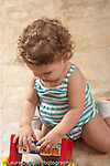 13 month old baby girl at home kneeling on floor exploring colorful wooden new toy turning pieces vertical