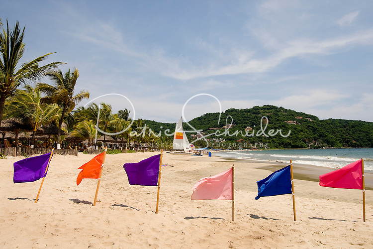 Colorful flags advertise parasailing operations along Playa la Ropa Beach, located on Zihuatanejo Bay. The beach is one of the most popular beaches in Zihuatanejo/Ixtapa.  (taken August 2007). Photo by Patrick Schneider Photo.com