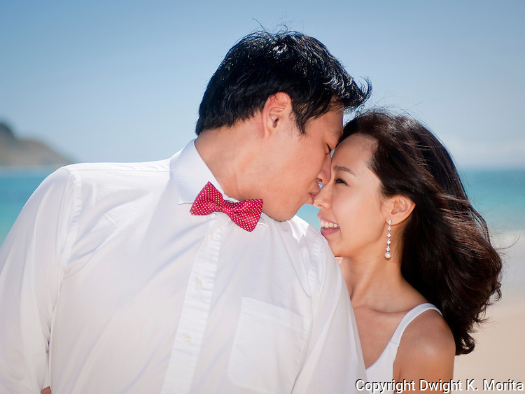 Asian bride and groom gaze at each other while they stroll on Lanikai beach as they look forward to their life as a married couple following their wedding.