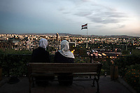Two women look out at the cityscape at a viewpoint overlooking Damascus, Syria.