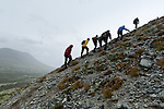 A group of hikers work their way up a hillside during a rainstorm in Norway's mountains.