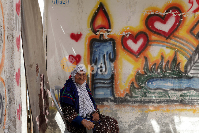 """A Palestinian elderly woman sits in front of her home in al-Shatee refugees camp western Gaza city, on march 13, 203. Israel is trying to go through the UN to change the legal nature of Palestinian refugees and deny """"refugee"""" status from the Palestinians who were forced to leave their homeland in 1948, The Department of Refugees' Affairs in Hamas movement said. Photo by Ashraf Amra"""