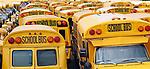 Yard full of school buses.