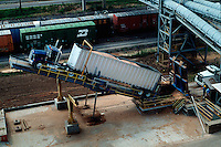 Aerial view of woodchips being dumped from a truck at a paper mill.