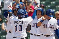 Round Rock Express shortstop Jurickson Profar #10 is greeted by teammates (L to R) Engle Beltre, Chris McGuiness, and Mike Olt after he blasted a grand slam home run the seventh inning of the Pacific Coast League baseball game against the New Orleans Zephyrs in the on April 21, 2013 at the Dell Diamond in Round Rock, Texas. Round Rock defeated New Orleans 7-1. (Andrew Woolley/Four Seam Images).