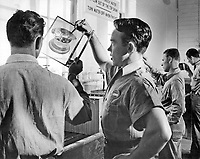 """Instructor L. H. Reed, PhoM 2/c criticizes 8""""x10"""" negative still in hanger as student lifts it from the washing tanks.  In background other students examine their processed negatives. Class II Advanced Ground Photography."""