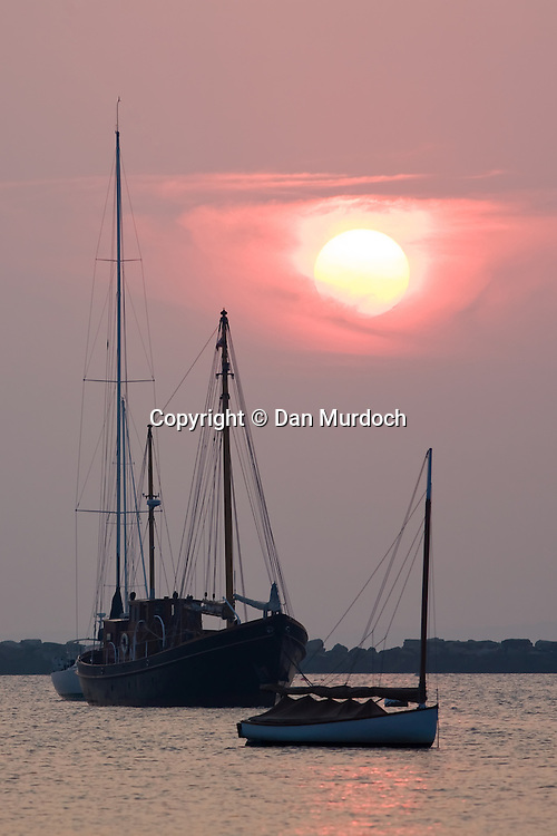 A red sunrise over boats in harbor