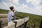 From the canopy tower at Myakka River State Park in Florida, a boy looks through the binoculars at the seemingly never-ending stretch of trees that cover this Florida landscape.