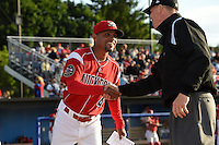 Batavia Muckdogs manager Angel Espada (4) shakes hands with umpire Chris Graham during the lineup exchange before a game against the Auburn Doubledays on June 14, 2014 at Dwyer Stadium in Batavia, New York.  Batavia defeated Auburn 7-2.  (Mike Janes/Four Seam Images)