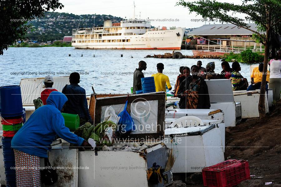 TANZANIA Mwanza, Lake Victoria, ship MV Victoria in port, in front fish seller offer Nile perch / TANSANIA Mwanza, Viktoria See, Schiff MS Victoria im Hafen, im Vordergrund Fischverkaeufer bieten Nilbarsch in alten Gefiertruhen an